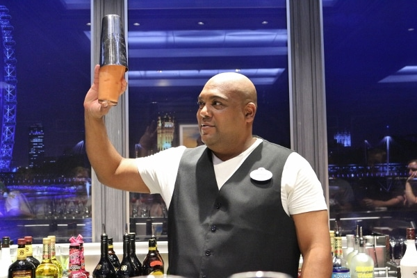 A man behind a bar holding up a cocktail shaker