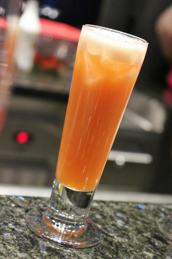 A closeup of a tall glass filled with an orange drink