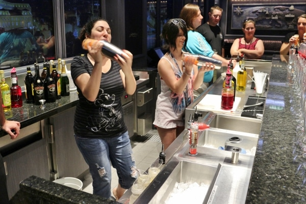 a group of people shaking drinks behind a bar