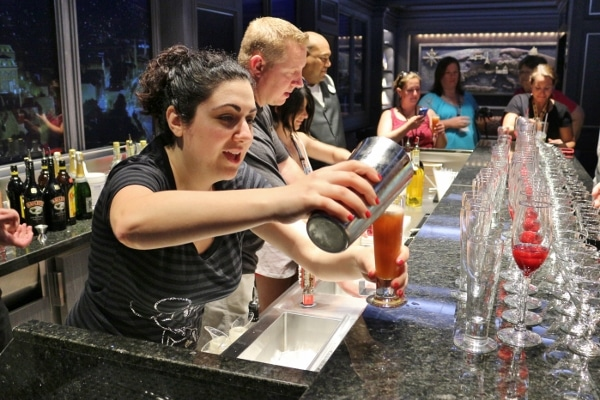 a closeup of a woman pouring a drink behind a bar