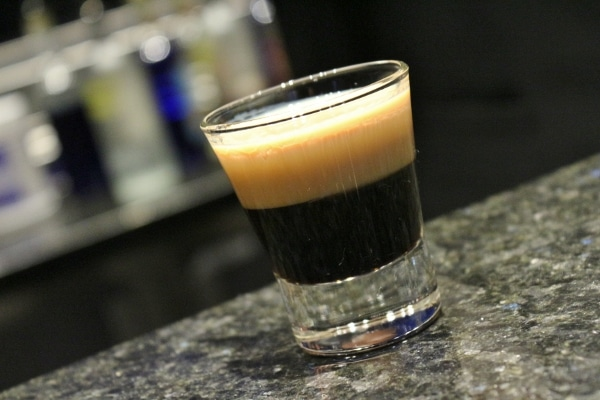 A closeup of a shot glass filled with a black drink with a foamy topping