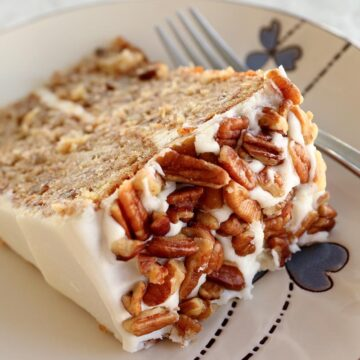 A slice of hummingbird cake with chopped pecans on a plate with a fork.