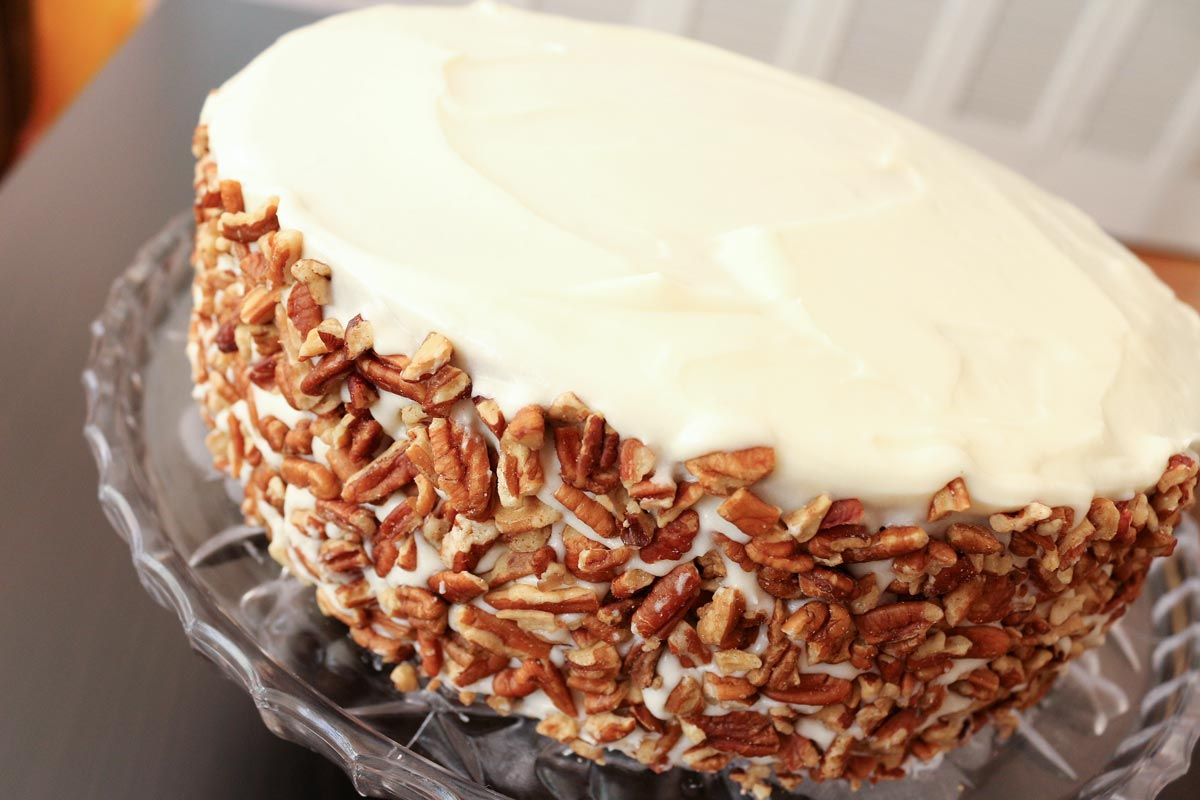 A layer cake with white frosting and chopped pecans around the sides on a glass cake pedestal.