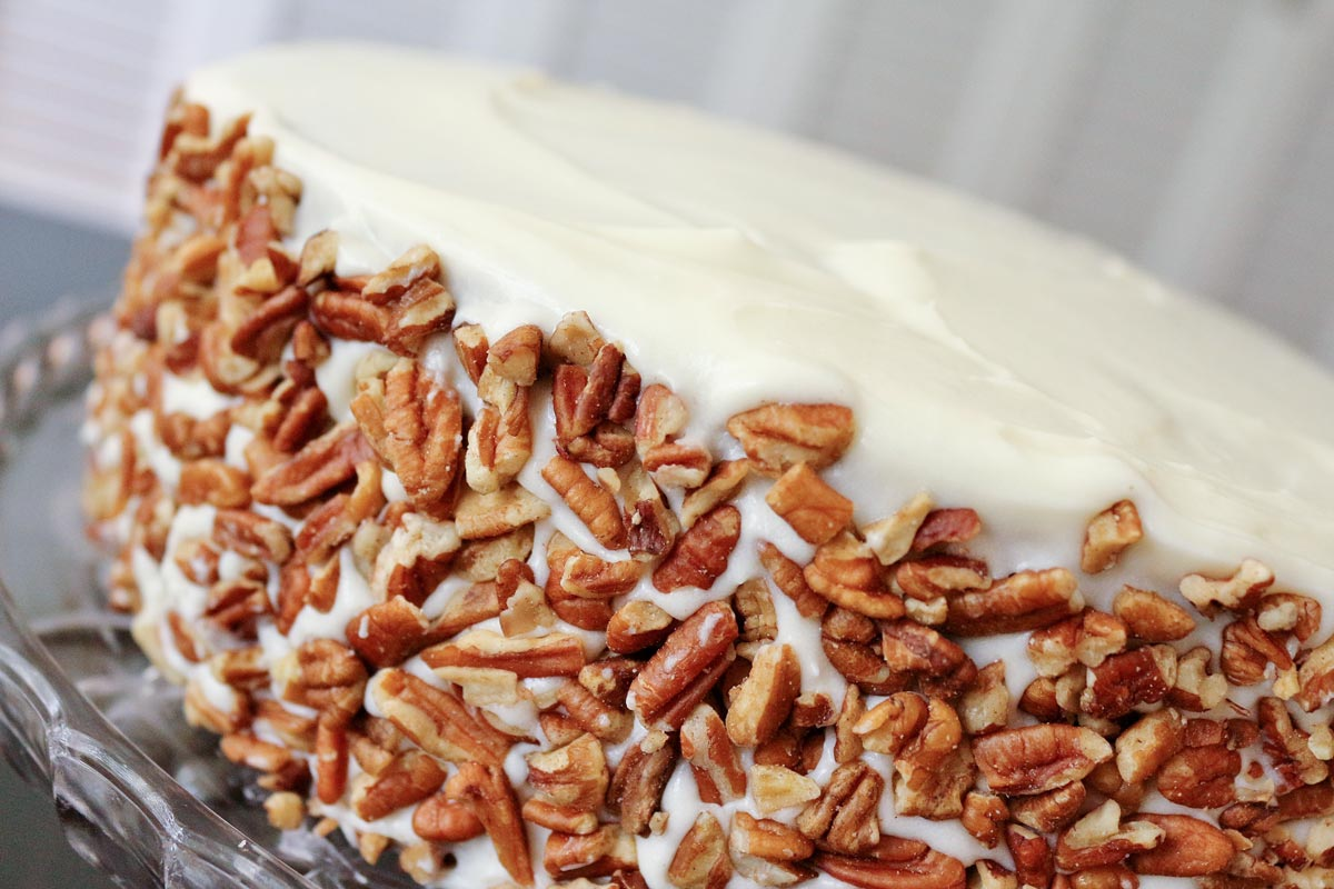 Closeup of a cake with white frosting and chopped pecans around the sides.