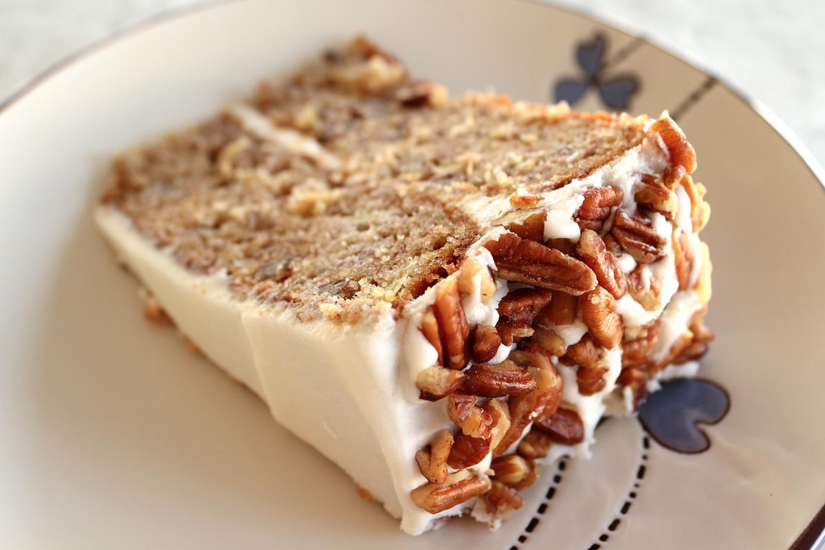A slice of cake with white frosting and pecans served on a plate.