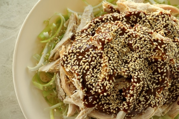 overhead view of shredded chicken topped with brown sauce and sesame seeds