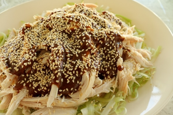 side view of a platter of chicken pieces topped with brown sauce and sesame seeds