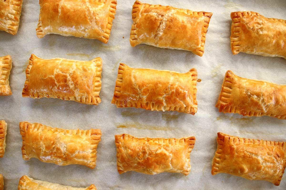 Rectangular golden puff pastry meat boreks on a baking sheet.