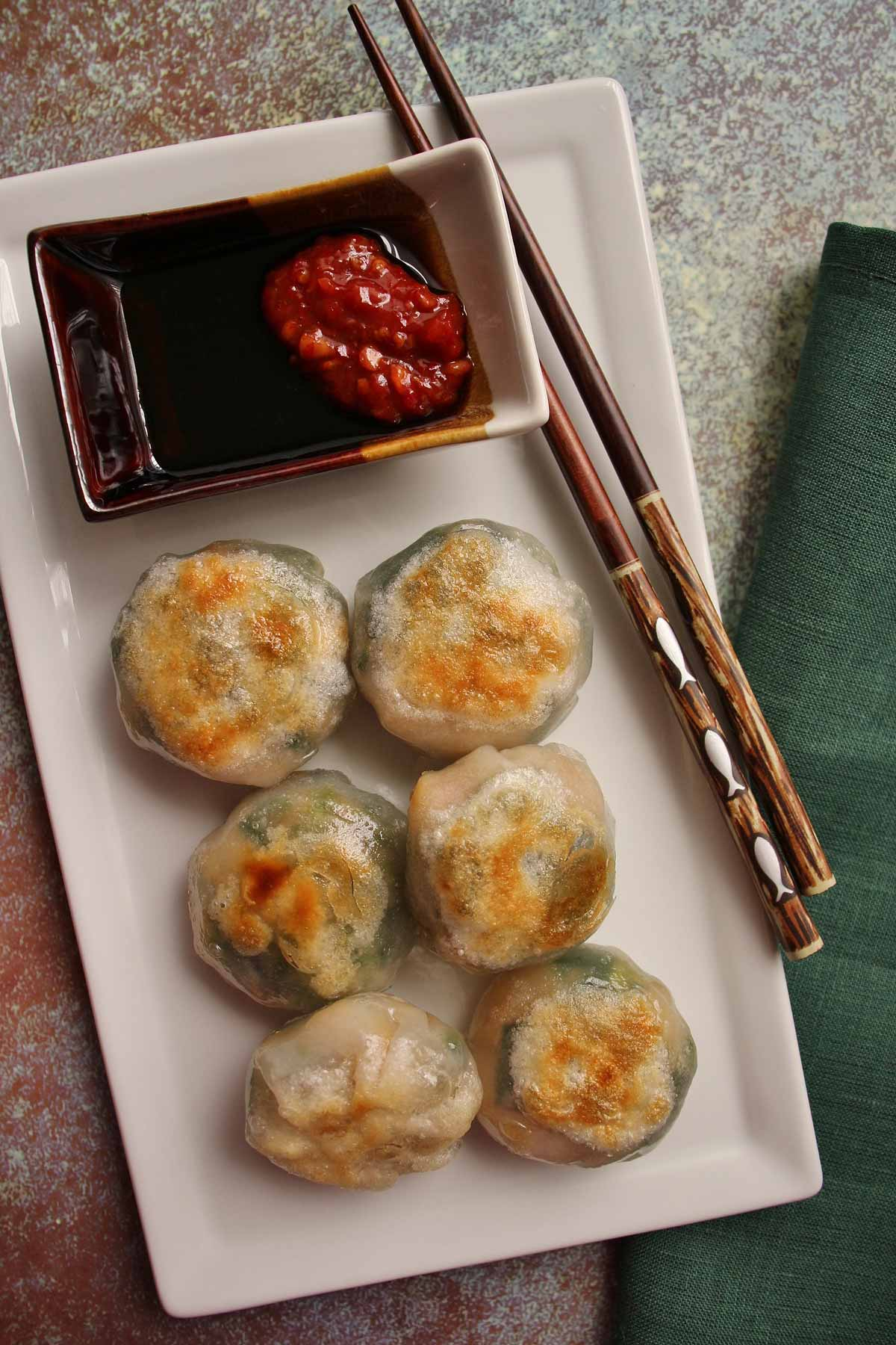 6 round pan-fried dumplings on a white rectangular plate with dipping sauce and chopsticks.