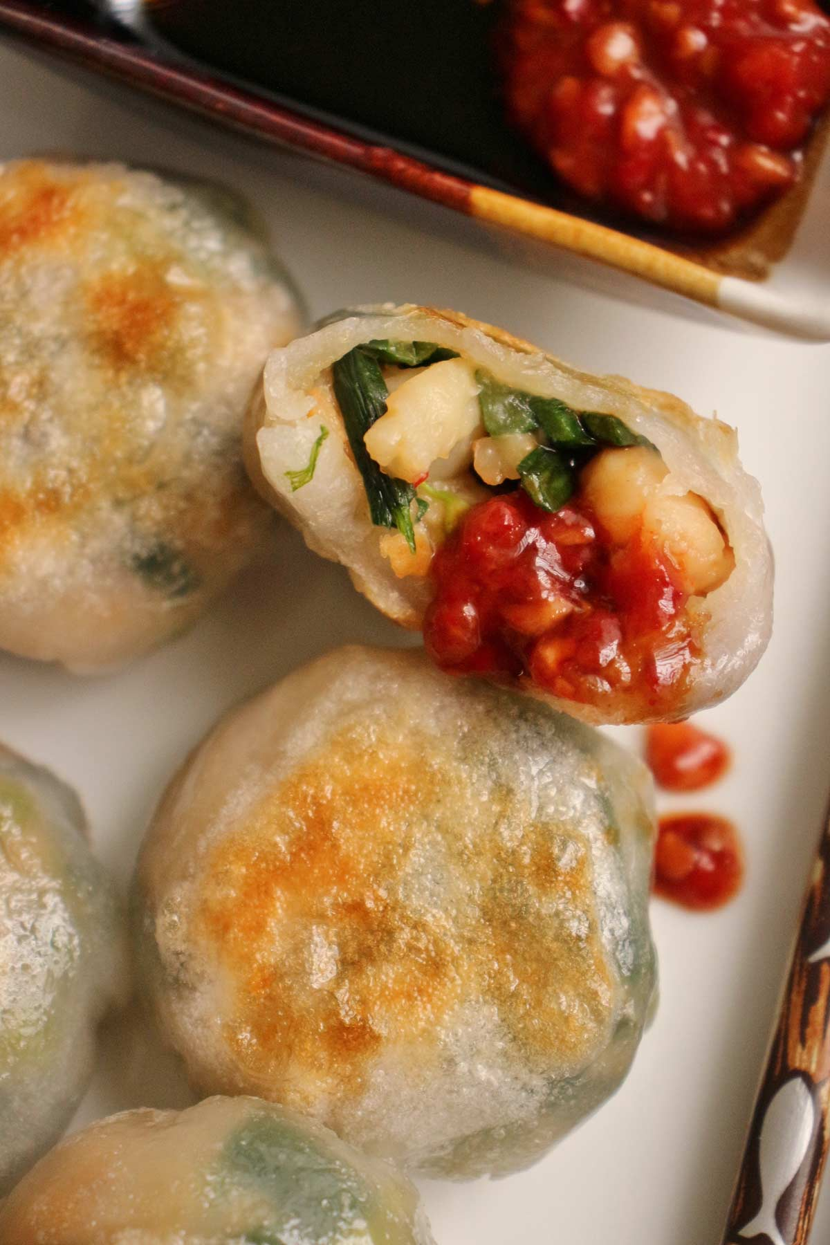 Closeup of a half eaten shrimp and chive dumpling with chile garlic sauce dripping down.