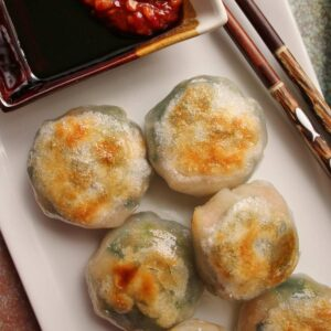 Closeup of pan-fried chive dumplings on a white rectangular plate with dipping sauce.