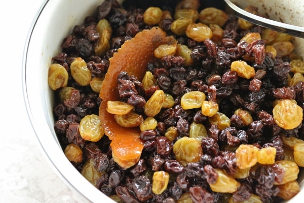 a bowl of red and yellow raisins with a big piece of orange zest