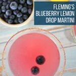 overhead view of a blueberry lemon drop cocktail with a bowl of blueberries, and a fresh lemon