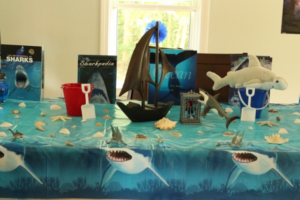 a table with a shark tablecloth topped with boat figurines and shark decorations