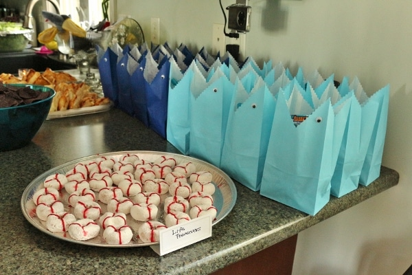 life preserver shaped donuts and shark shaped blue gift bags on a counter