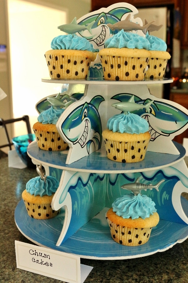 a tiered cupcake display with shark and ocean illustrations on it