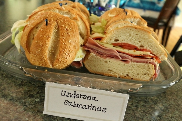 a platter of sandwiches with a sign that says Undersea Submarines
