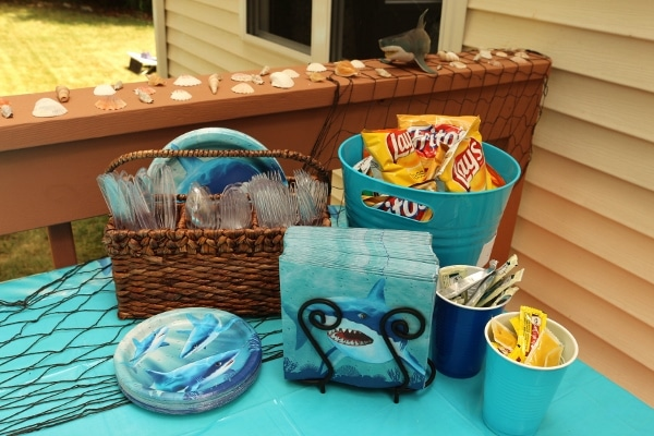 a shark themed buffet table setup with napkins, plates, and a bucket of chips