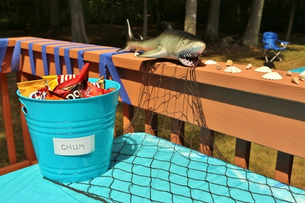 a shark themed table display with a bucket of chips labeled as chum