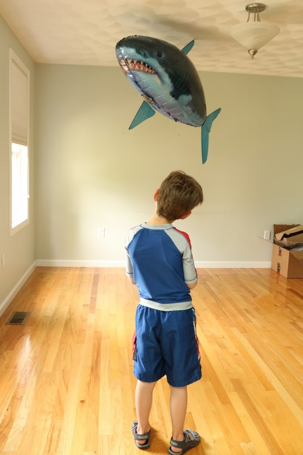 A young boy standing on top of a hard wood floor with a floating shark overhead