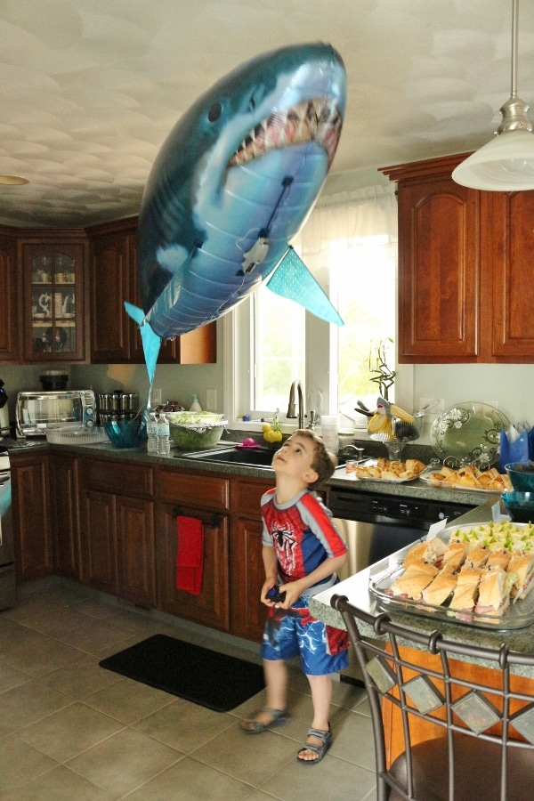 A boy standing in a kitchen with a floating shark overhead