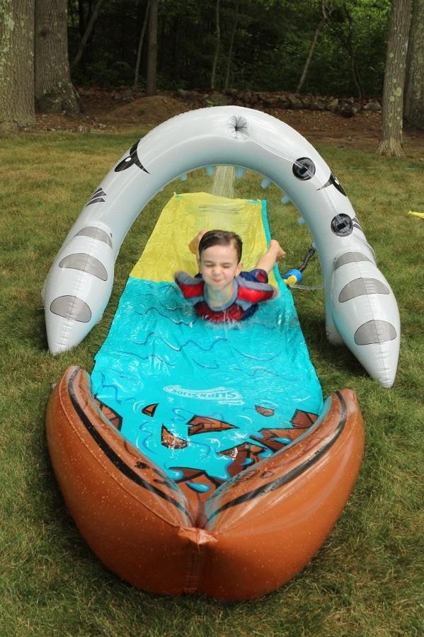 a boy sliding down a shark themed yard water slide on the grass