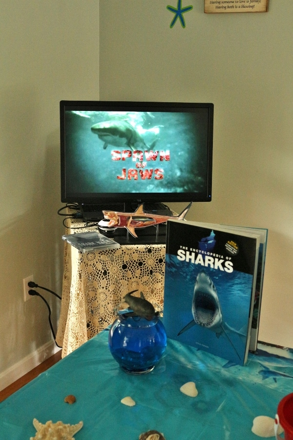 A television with a shark on it and shark decorations in front of it