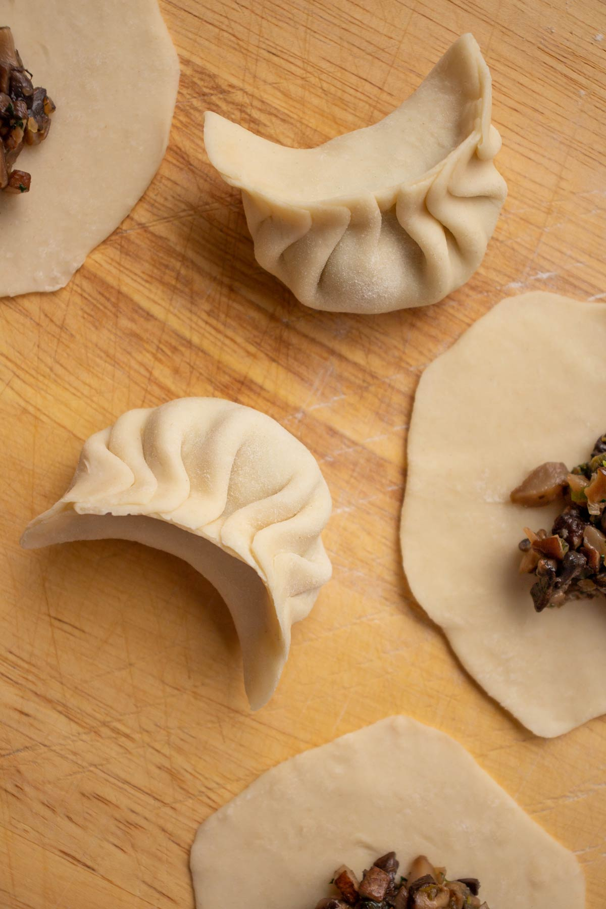 Two pleated dumplings on a wooden surface.