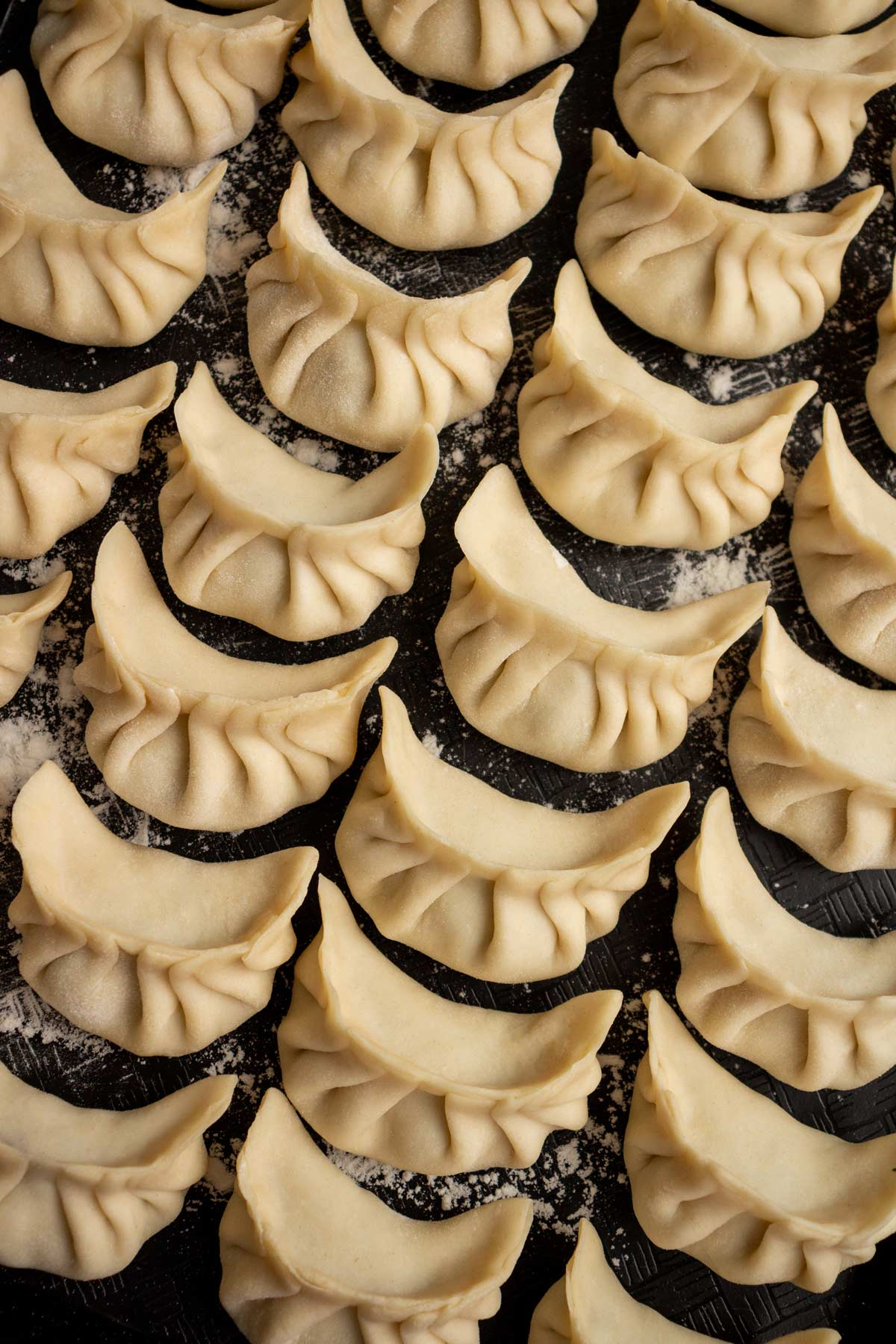 Rows of pleated dumplings on a black surface.