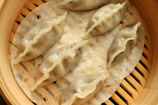 overhead view of six steamed dumplings in a bamboo steamer basket