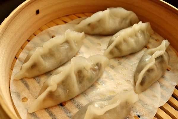 side view of six steamed dumplings in a bamboo steamer basket