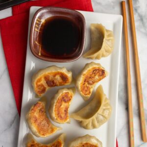 Mushroom dumplings on a white rectangular dish with a bowl of dipping sauce on the side.