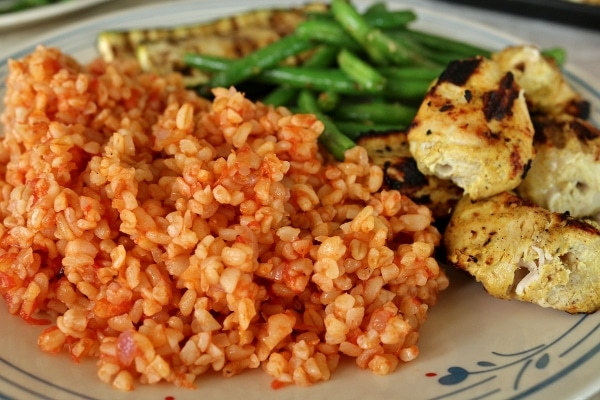 A plate of grilled chicken, tomato bulgur pilaf, and green beans