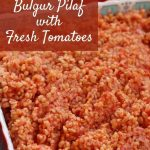 bright red bulgur pilaf with tomatoes in a square dish