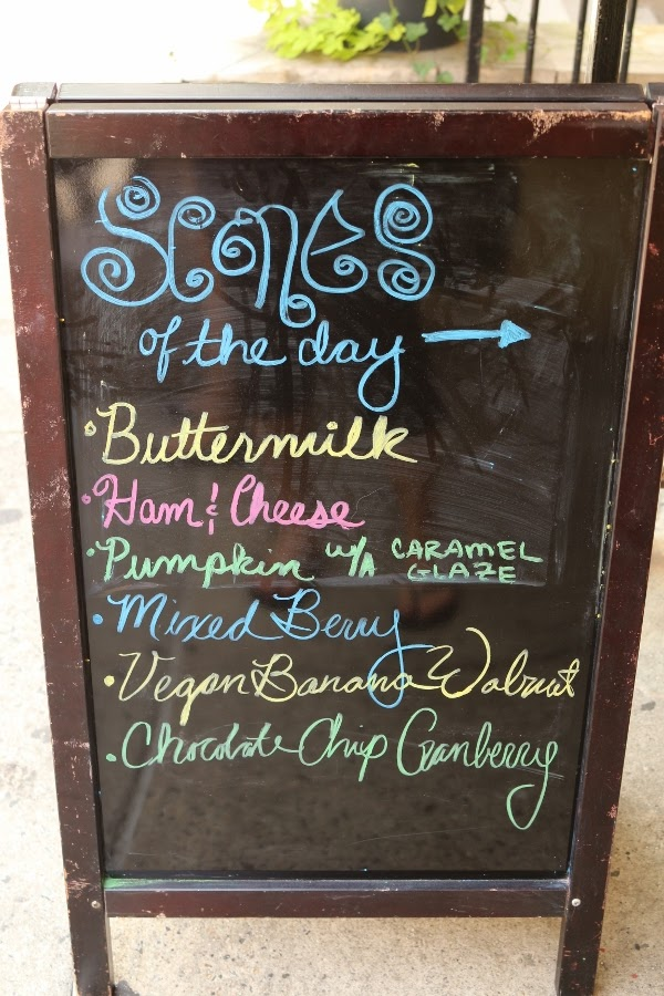 A blackboard sign that says Scones of the Day with a list of flavors
