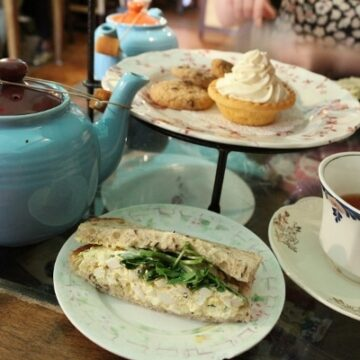 a sandwich on a plate next to a blue teapot and white teacup filled with tea
