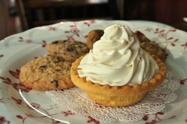 a plate of cookies and a small cream topped tart