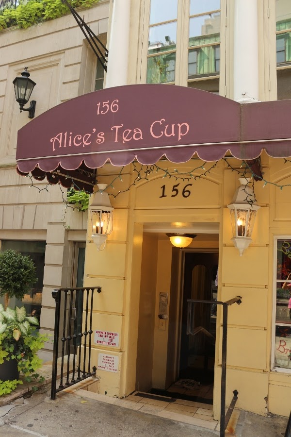 A sign on the side of a building that says Alice\'s Tea Cup