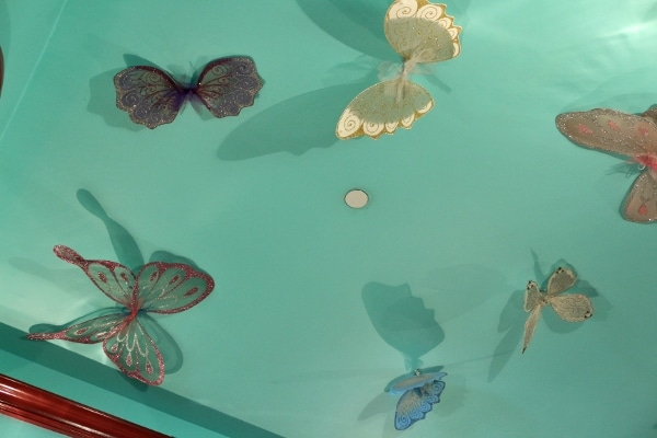 butterfly wing decorations on a turquoise ceiling