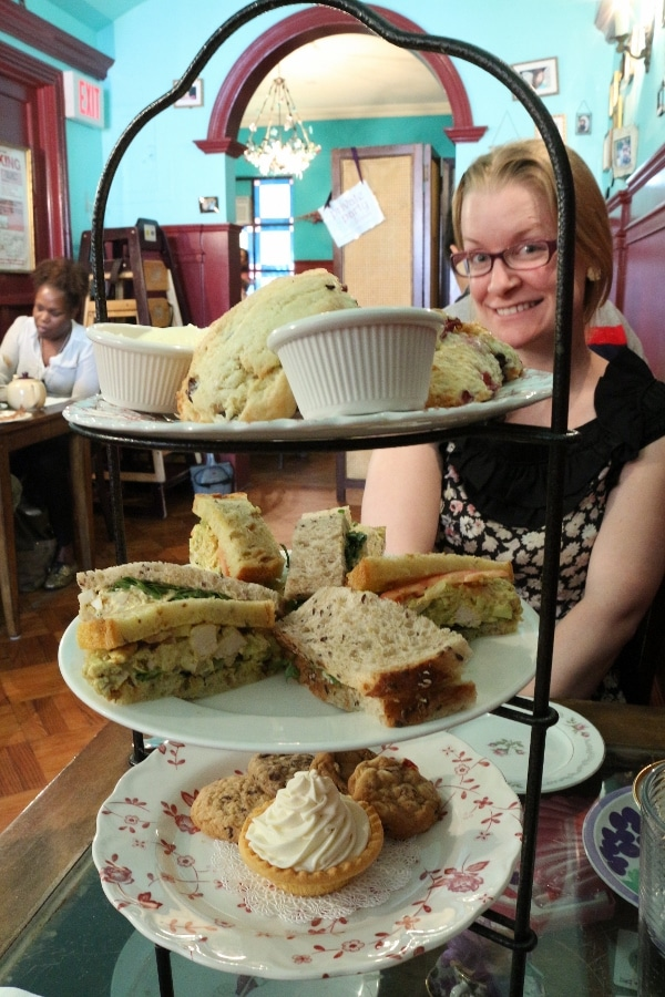 a three-tiered afternoon tea display of food with a woman on the other side