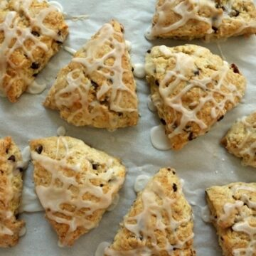 overhead view of triangular scones with glaze drizzled on top on a baking sheet