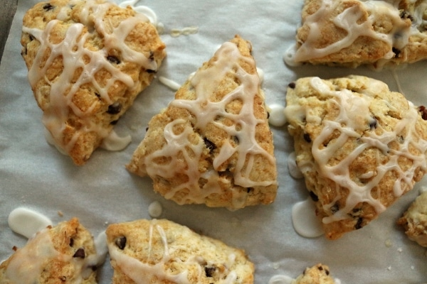 overhead closeup of triangular glazed scones on a parchment paper lined baking sheet