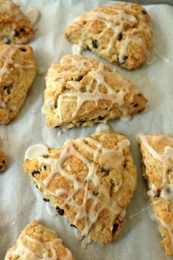 triangular scones topped with drizzled glaze on a parchment paper lined baking sheet
