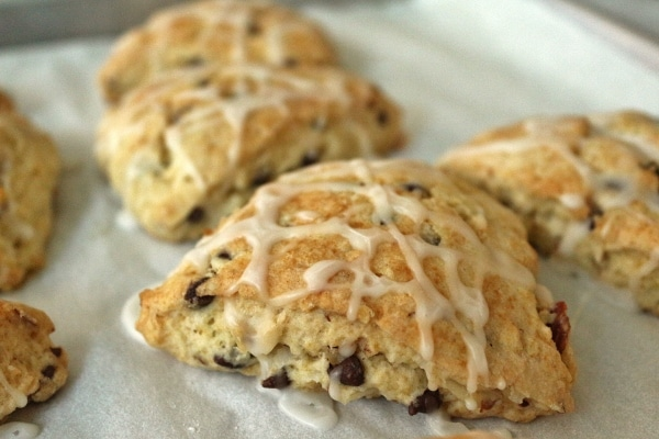 A closeup of a scone with chocolate chips topped with drizzled glaze