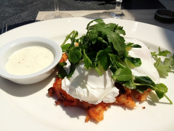 poached eggs topped with greens served over lobster hash on a white plate