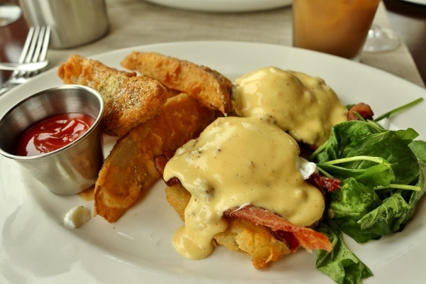 a plate of Eggs Benedict made with fried green tomatoes, served with fried potato wedges