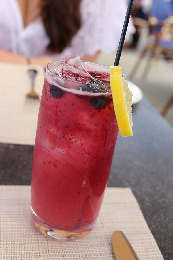 a tall glass filled with a bluish drink topped with floating blueberries and a lemon slice