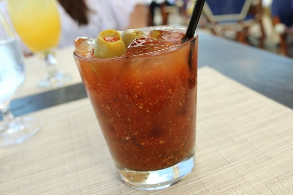 a bloody mary with a green olive garnish in a short glass with a black straw