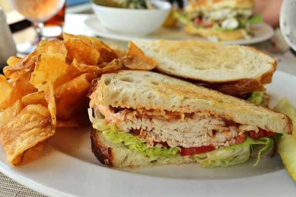 A closeup of a sandwich on a plate with potato chips on the side