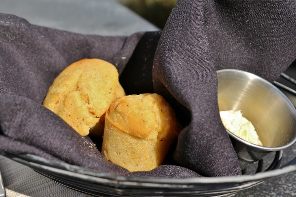 two corn muffins in a bread basket with a black cloth napkin